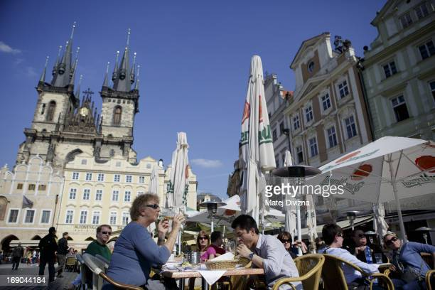 A woman drinks beer as a man eats meal in the Old Town Square with Tyn Church in the background on April 24 2013 in Prague Czech Republic Prague is...