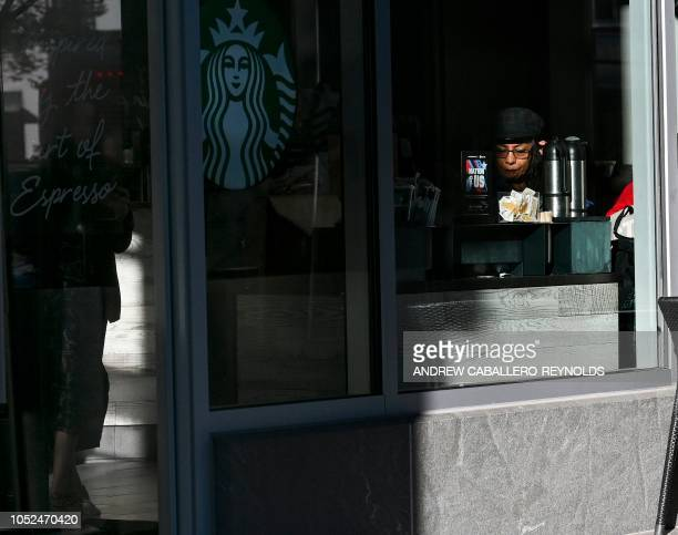 A woman drinks coffee at a Starbucks coffee shop in Washington DC on October 18 2018