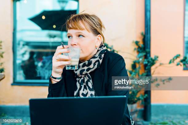 Woman drinks coffee in front of laptop while sitting at cafe