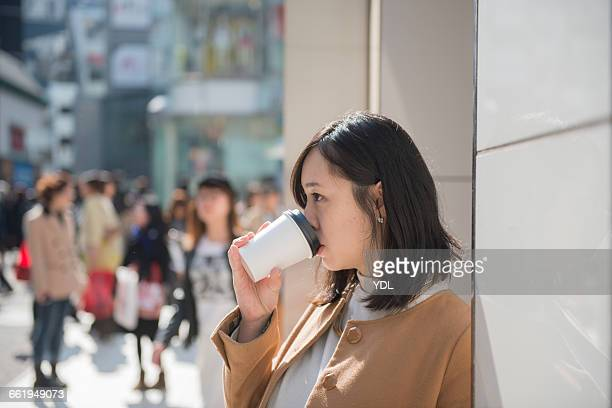 A woman drinks coffee on lively street.