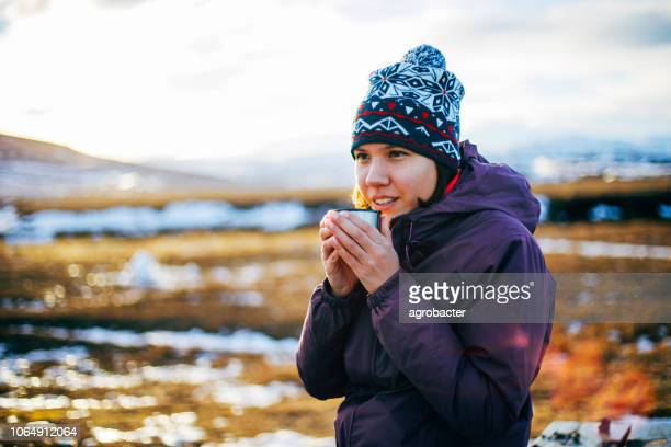 woman drinks hot tea or coffee - non urban scene stock pictures, royalty-free photos & images