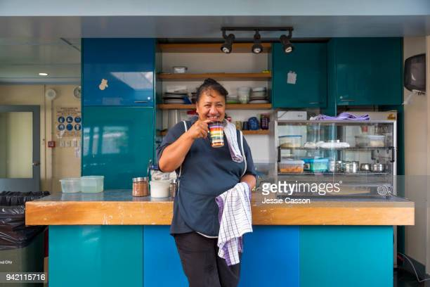 A woman drinks tea in a factory cafeteria