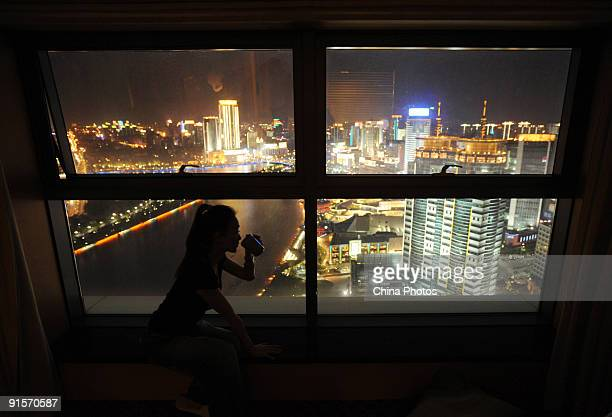 A woman drinks tea with the background of illuminated downtown area on October 7 2009 in Ningbo of Zhejiang Province China Ningbo a cultural and...