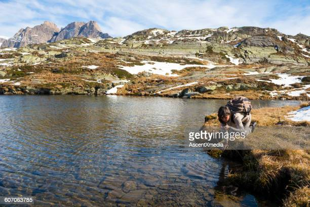 Woman drinks water from mountain pond