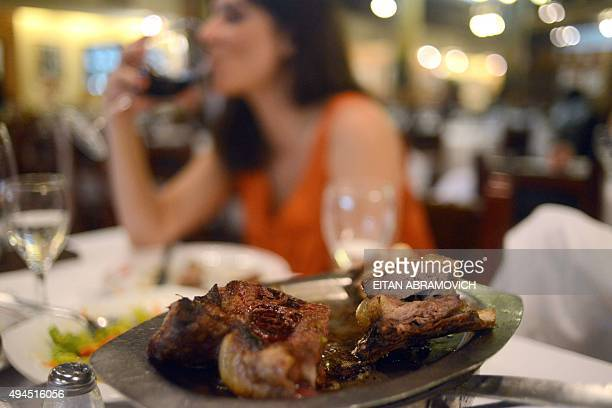 A woman drinks wine while eating beef at a traditional grill restaurant in Buenos Aires on October 27 2015 Sausages ham and other processed meats...