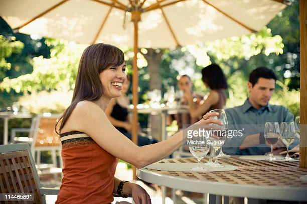 a woman drinks wine with friends at a garden table - healdsburg stock pictures, royalty-free photos & images