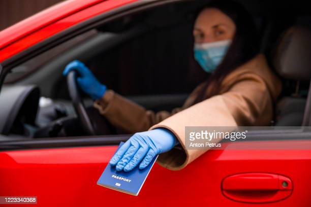 woman driver in medical face mask and gloves handing over immunity passport through car window - national border stock pictures, royalty-free photos & images