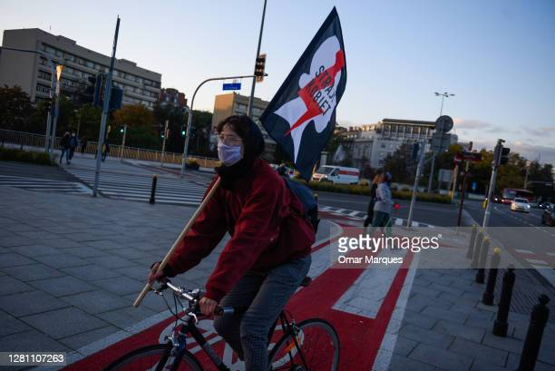 Woman drives a bicycle with the National Women's strike flag during a protest against the Constitutional Tribunal decision for tightening the current...
