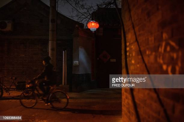 A woman drives on a bicycle in a 'Hutong' a traditional Beijing courtyard ahead of the upcoming Lunar New Year in Beijing on February 3 2019