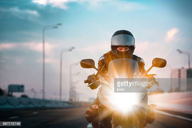 woman drives on a motorcycle on a morning highway - drive sportbegriff stock-fotos und bilder