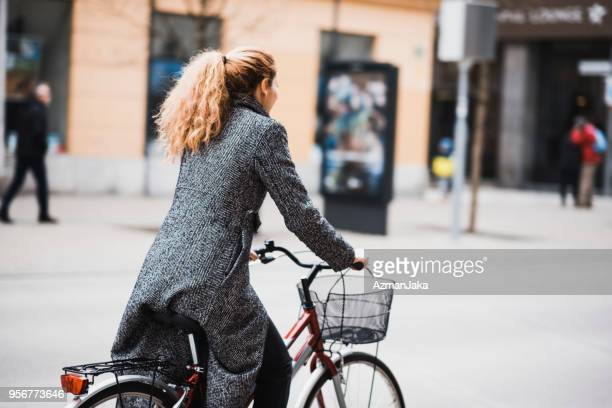 woman driving a bike in the city - bicycle parking station stock photos and pictures