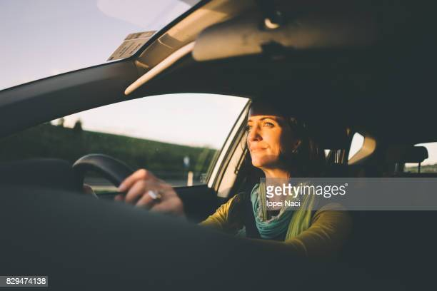 Woman driving a car at sunset, Melbourne