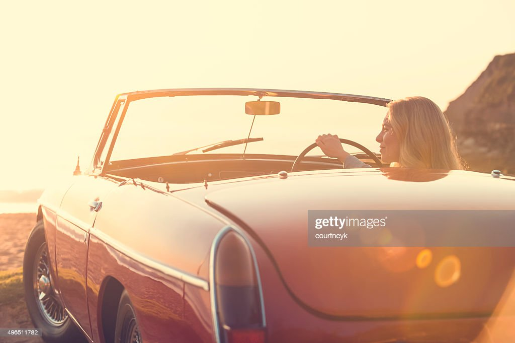 Woman driving a convertible car at the beach. : Stock Photo