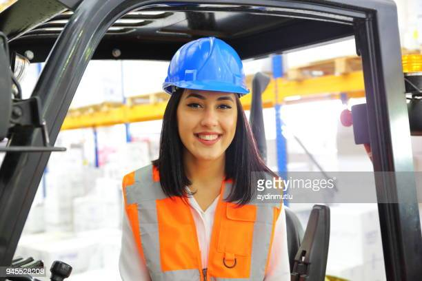 woman driving a forklift at distribution warehouse - jacket stock pictures, royalty-free photos & images