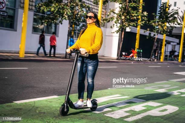 a woman driving an electric scooter on a scooter & bike lane in the city downtown - mobility scooter stock photos and pictures