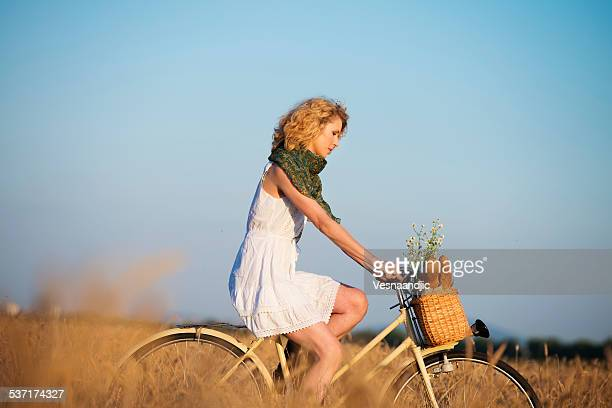 Woman driving bicycle through wheat field