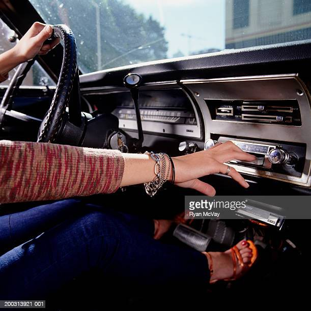 Woman driving car, hand tuning radio,  mid section