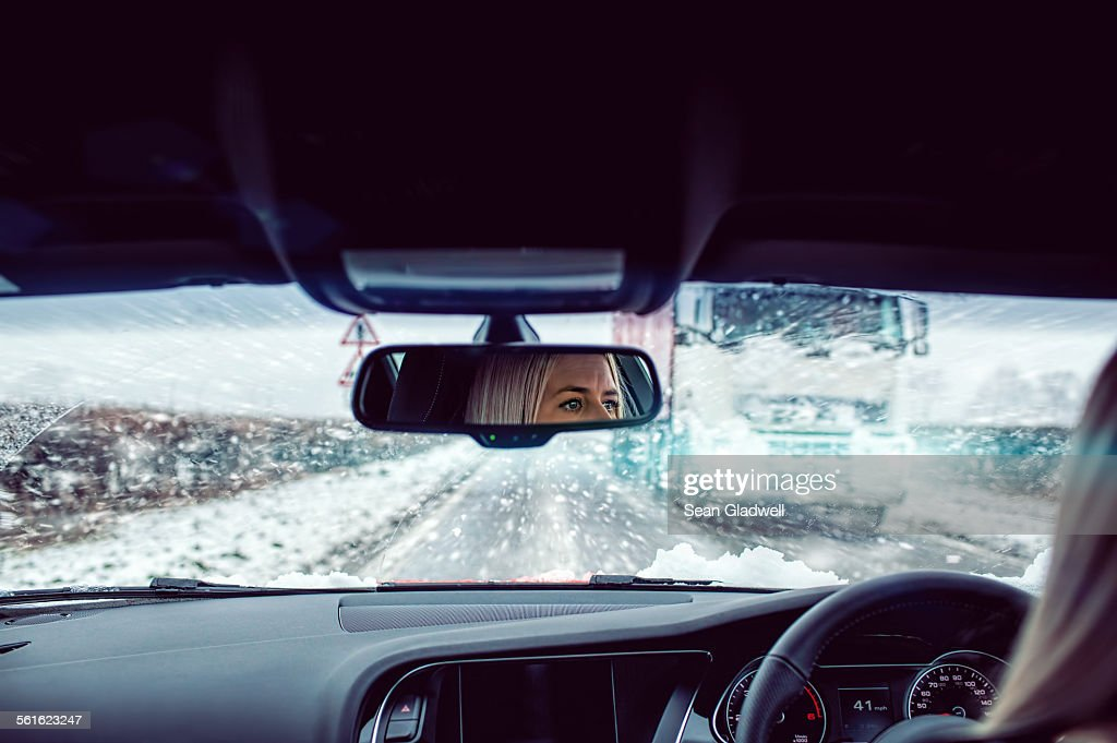 Woman driving car in snow : Stock Photo