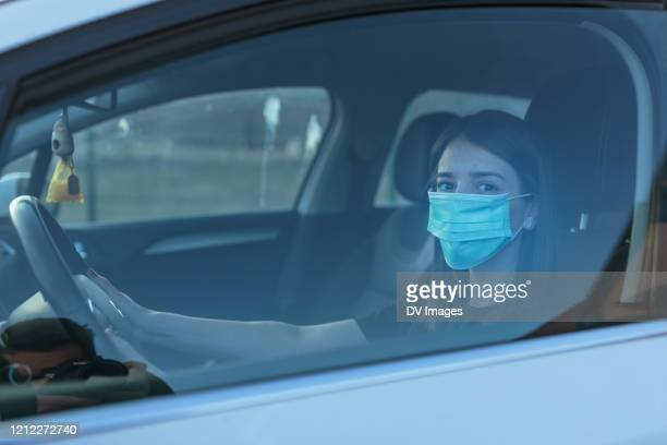 woman driving car while wearing protective mask - driving mask stock pictures, royalty-free photos & images