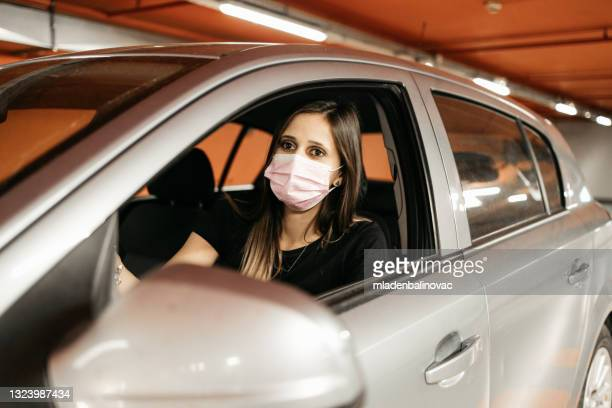 woman driving car while wearing protective mask - luggage hold stock pictures, royalty-free photos & images
