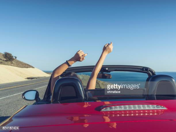 Woman driving car with arm in the air feeling the breeze