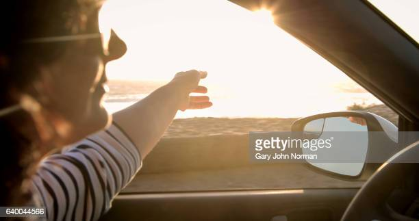 woman driving car with arm out of window feeling the breeze - side view mirror stock photos and pictures