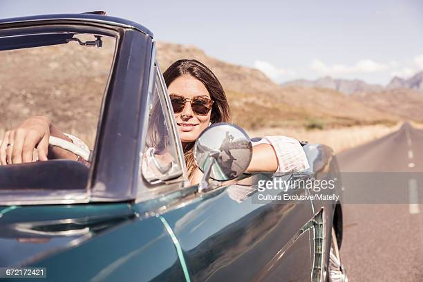 Woman driving classic convertible car, Cape Town, South Africa