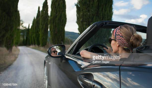 woman driving convertible car on tuscan country road, italy - convertible stock pictures, royalty-free photos & images