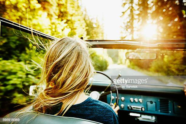 Woman driving convertible on summer evening
