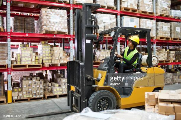 woman driving forklift in warehouse - forklift stock pictures, royalty-free photos & images