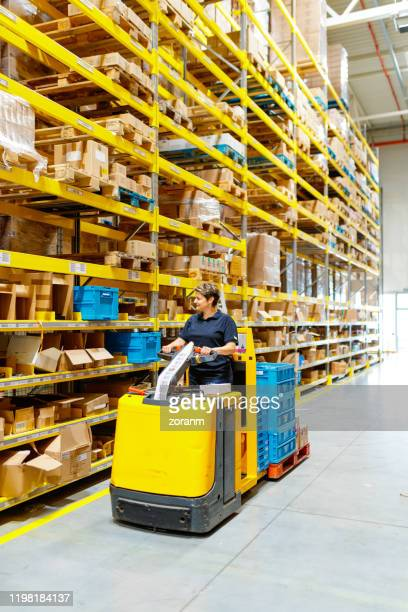 woman driving forklift through aisle in warehouse - industrial storage bins stock pictures, royalty-free photos & images