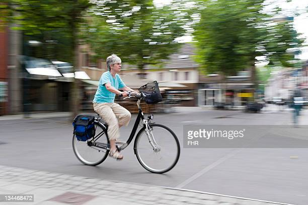 Woman driving her bike across the marketplace, Grevenbroich, North Rhine-Westphalia, Germany, Europe
