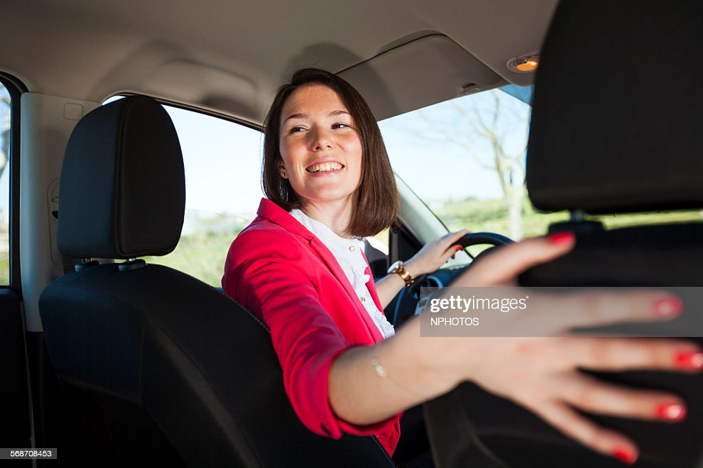 Woman driving her car in reverse : Stock Photo