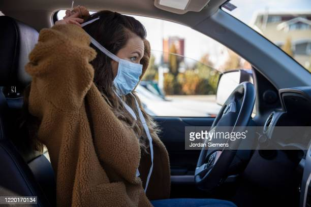 a woman driving her vehicle wearing latex gloves and a mask during the covid-19 pandemic. - driving stock pictures, royalty-free photos & images