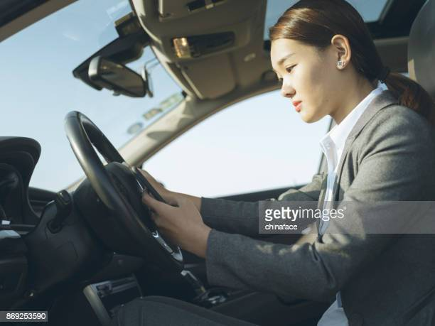 woman driving in car and texting on cellphone