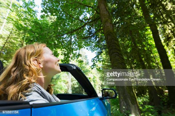 Woman driving in convertible looking up at trees in forest
