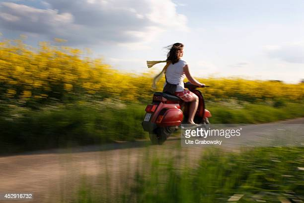 Woman driving on a vespa past a canola field on May 06 in Bonn Germany