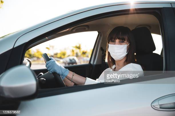 woman driving to work during pandemic days - state of emergency stock pictures, royalty-free photos & images