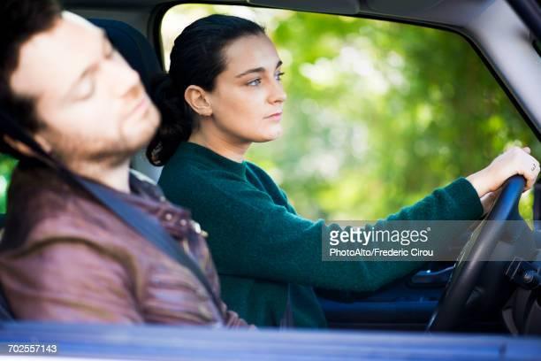 Woman driving while companion naps