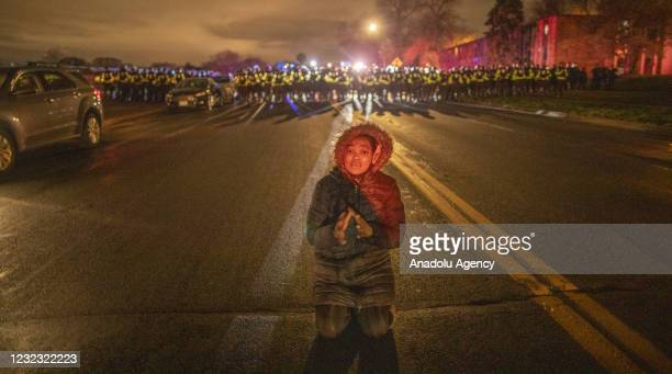 Woman dropped to her knees as a line of police stand behind her sent in to clear the area and make arrests of protesters, in Minnesota, United States...