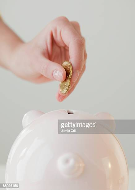 Woman dropping coins in piggy bank