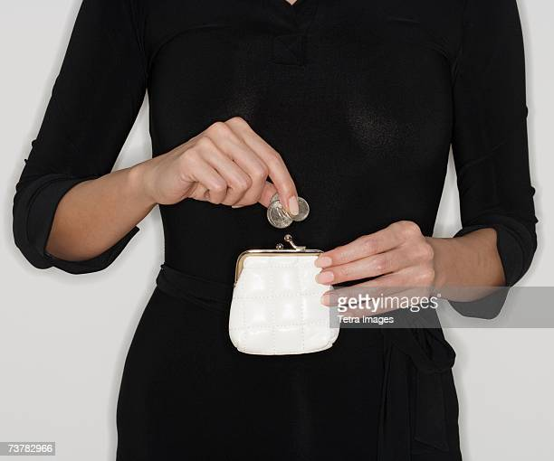 Woman dropping coins in purse