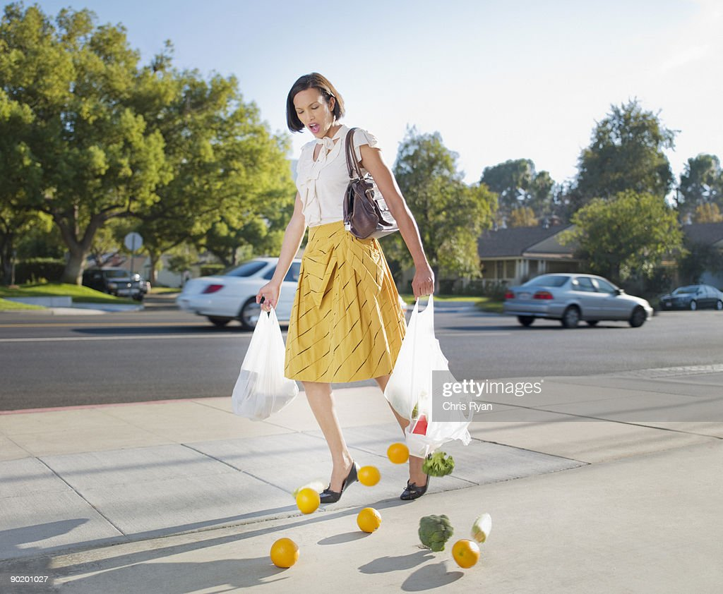 Woman dropping groceries on sidewalk : Stock Photo