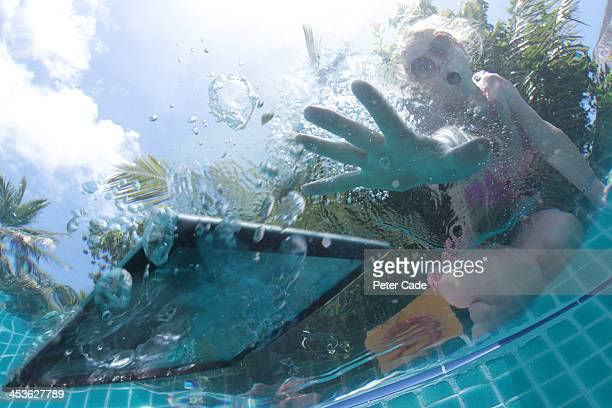 Woman dropping tablet into swimming pool