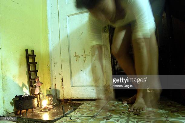 A woman drops coins in front an altar December 3 2002 in Isla de la Juventud Cuba Adherents of Santeria a religion whose origins date back to the...