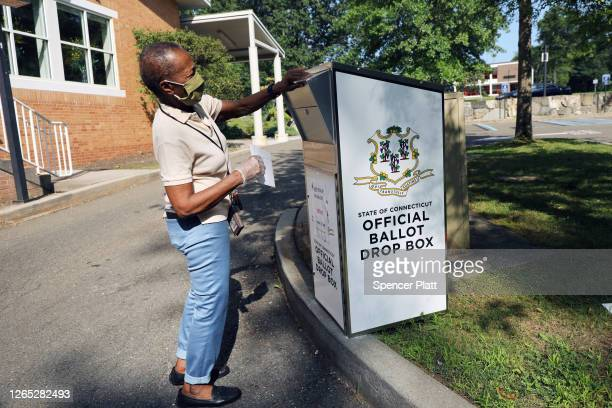 A woman drops her Connecticut 2020 presidential primary ballot at a secure ballot drop box at a Stamford library on August 11 2020 in Stamford...
