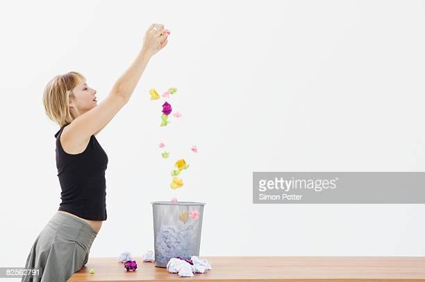 Woman drops paper into bin