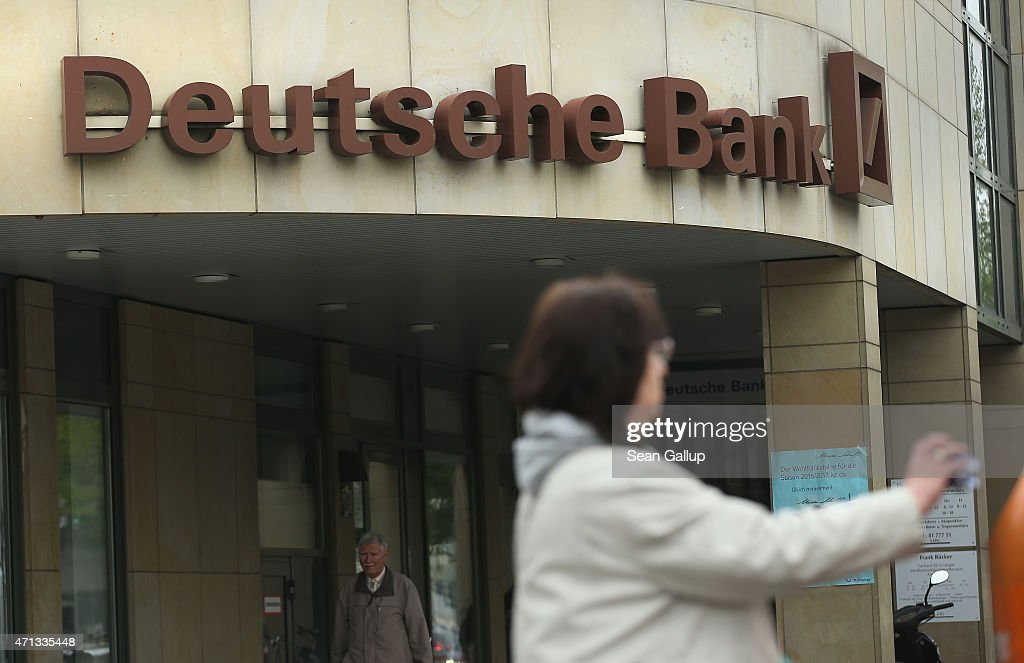 A woman drops refuse into a trash can next to a branch of German bank Deutsche Bank on April 27, 2015 in Berlin, Germany. Deutsche Bank announced earlier in the day that it will close 200 of its 700 branches in Germany over the next two years in an effort to save an annual EUR 3.5 billion.