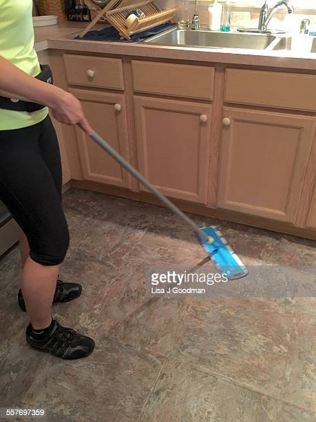 Woman Dry Mopping Kitchen Floor