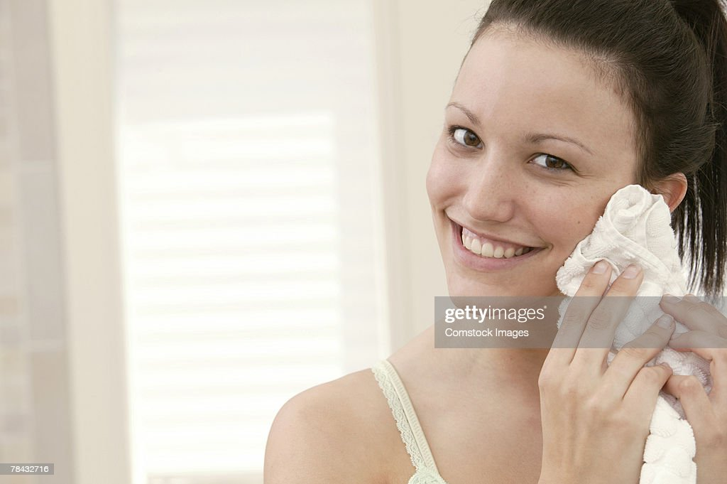 Woman drying face with towel : Stockfoto
